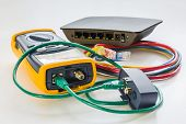 network tester and small switch with various color RJ45 cables 5e connected for testing poster