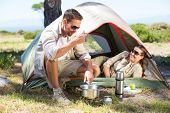 Outdoorsy couple cooking on camping stove outside tent on a sunny day poster
