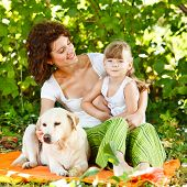 Beautiful mother and daughter relaxing in nature with their dog poster