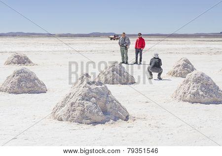 Tourists family posing among salt piles at Salar de Uyuni, Bolivia