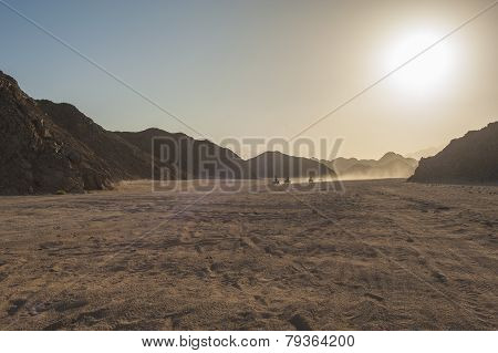 Group of quad bike atv vehicles traveling through rocky desert on safari with sunset poster