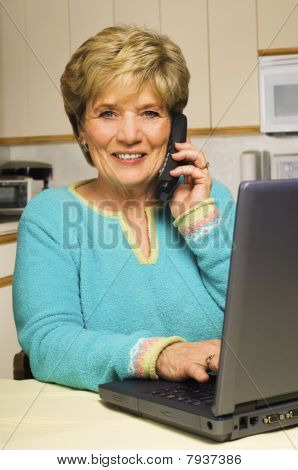 Woman Talks On Phone While Working On Laptop