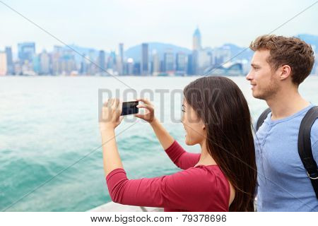 Tourist couple taking photo pictures enjoying view and sightseeing on Tsim Sha Tsui Promenade and Avenue of Stars in Victoria harbour, Kowloon, Hong Kong. Tourism travel concept. poster