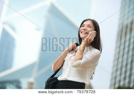 Business woman talking on smart phone in Hong Kong. Asian business people office worker talking on smartphone smiling happy. Young multiracial Chinese Asian / Caucasian female professional outside.