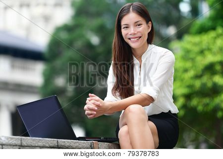 Business people - woman on laptop in Hong Kong. Businesswoman on computer and internet outside in Central Hong Kong. Young female professional business woman smiling. Asian Chinese Caucasian woman.
