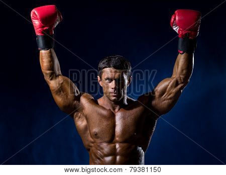 Strong Muscular Boxer In Red Boxing Gloves Raised His Hands Above His Head.