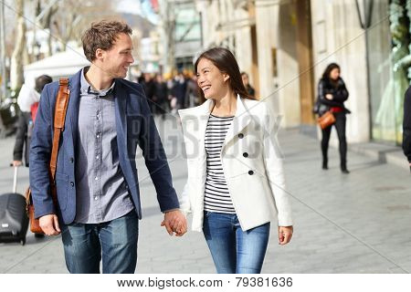 Urban modern professionals couple walking romantic laughing talking holding hands on date. Young multicultural couple Asian and Caucasian. From famous Passeig de Gracia, Barcelona, Catalonia, Spain.