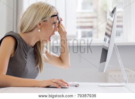 Shocked woman looking at computer