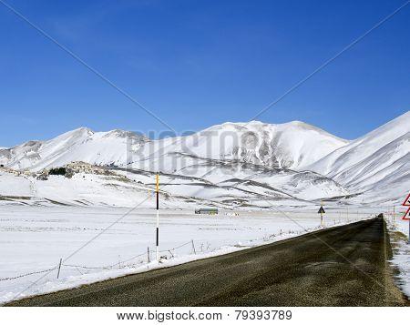 Asphalt Straight Road Along  Plateau Of Castelluccio Of Norcia In Winter,