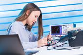 Girl repairing electronic device on the circuit board poster