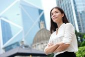 Business woman confident portrait in Hong Kong. Businesswoman standing proud and successful in suit cross-armed. Young multiracial Chinese Asian / Caucasian female professional in central Hong Kong. poster