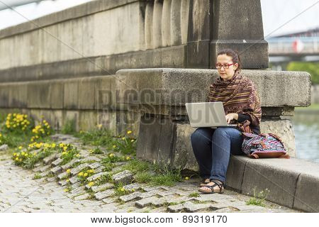 Young woman working on laptop while sitting near the river promenade in the old town.