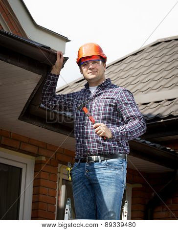 Handyman Standing On High Ladder And Inspecting House Roof