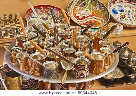 Turkish coffee pots also know as ibrik cezve and briki in a street maket with ceramic bowls in the background poster