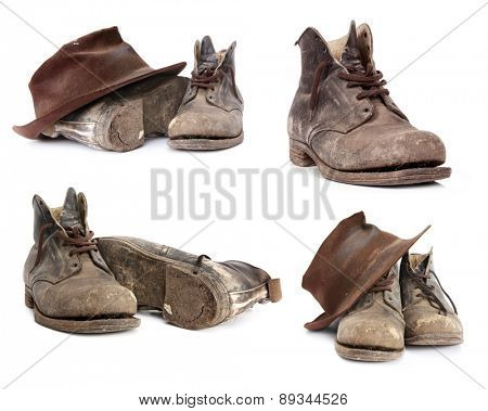 Old work boots and battered hat.  Collection isolated on white.