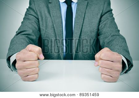 closeup of a young caucasian man wearing a gray suit banging his fists on his office desk