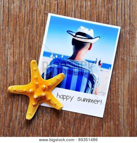 high-angle shot of a starfish and an instant photo, shot by myself, of a young man at the beach, with the text happy summer written in the frame, placed on a rustic wooden table