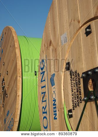 Large timber drums with green fiber optic cable