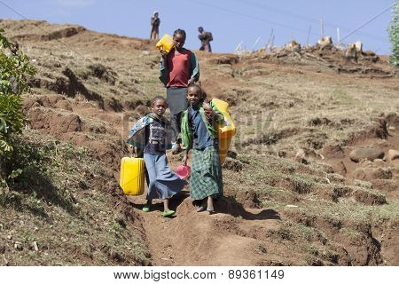 OROMIA, ETHIOPIA-APRIL 21, 2015: Unidentified children carry plastic containers on their way to a water source on April 21, 2015 in Oroma, Ethiopia.