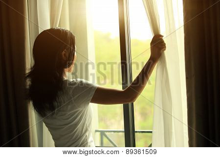 young woman opening curtains in a bedroom