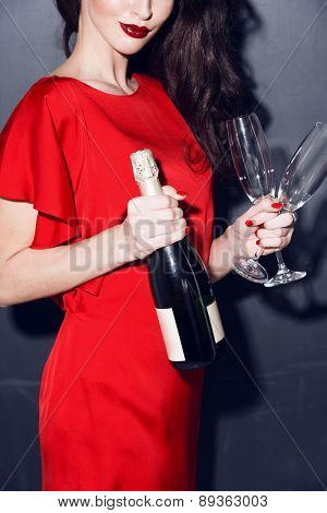 brunette in red dress with bottle of champagne and two glasses