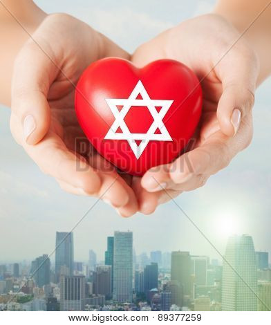 religion, christianity, jewish community and charity concept - close up of female hands holding red heart with star of david symbol over city skyscrapers background