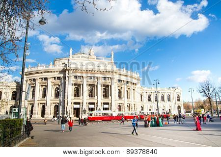 Front facade of Burgtheater, red tram and people on the square, Vienna