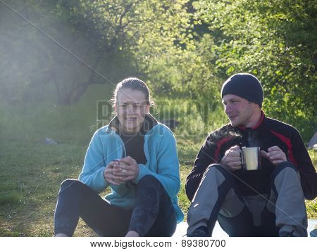 A Man And A Woman Drink From Mugs In Nature.