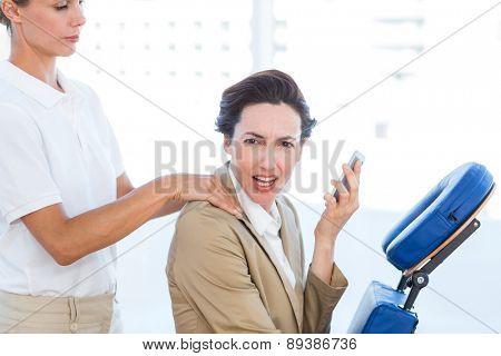Upset businesswoman having back massage in medical office