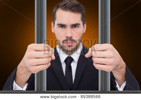 Exasperated businessman with clenched fists against orange background with vignette
