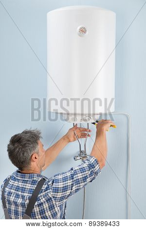 Portrait Of Happy Male Plumber Repairing Electric Boiler poster