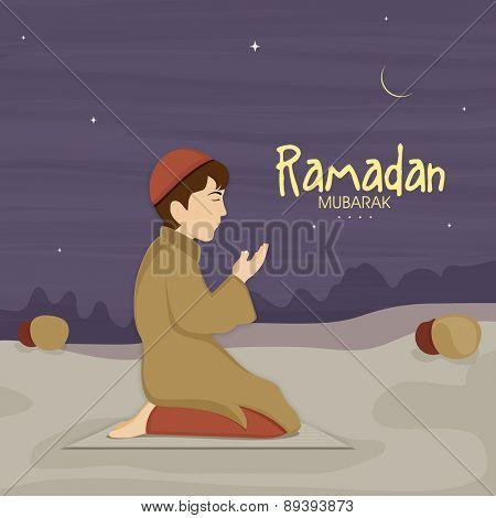 Cute little Muslim boy in traditional dress praying (reading Namaz, Islamic Prayer) in night on occasion of holy month Ramadan Kareem celebration.