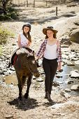 cute female kid jockey having fun learning riding pony outdoors happy with young Australian American horse instructor woman in cowboy look teaching the little rider in summer nature countryside poster