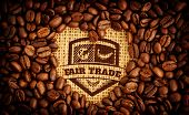 Fair Trade graphic against heart indent in coffee beans poster