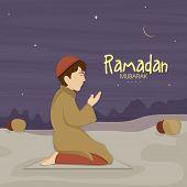 Cute little Muslim boy in traditional dress praying (reading Namaz, Islamic Prayer) in night on occasion of holy month Ramadan Kareem celebration.   poster