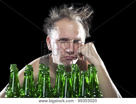 The tipsy man sits with a heap of beer bottles a hangover