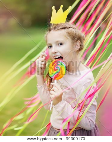 little girl with a paper crown and a bright lollipop