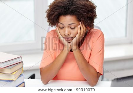people, technology and education concept - bored african american young woman sitting at table with books and thinking at home
