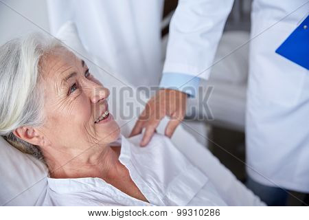 medicine, age, health care and people concept - doctor visiting happy senior woman at hospital