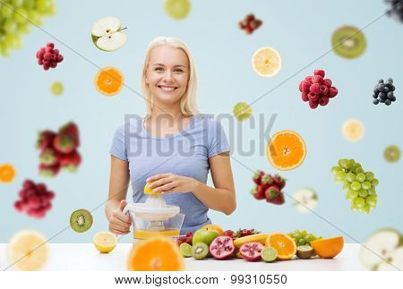 healthy eating, vegetarian food, diet, detox and people concept - smiling woman with squeezer squeezing fruit juice over fruits and berries on gray background