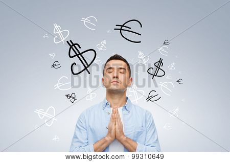 finance, business, faith and people concept - happy man with closed eyes praying to god with money currency symbols over gray background
