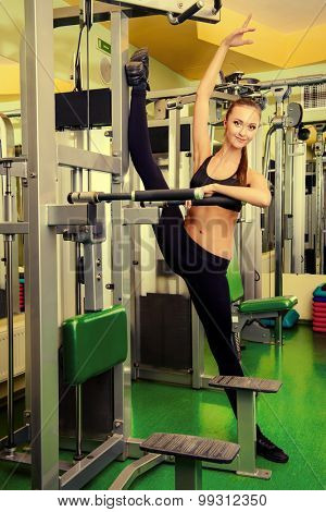 Slender girl doing stretching exercises at the gym. Active lifestyle, bodycare. Perfect figure. poster