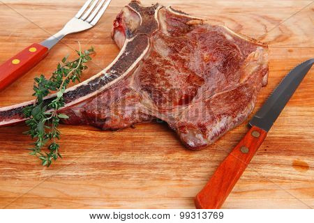 savory : roasted beef spare rib on wooden plate with cutlery and thyme