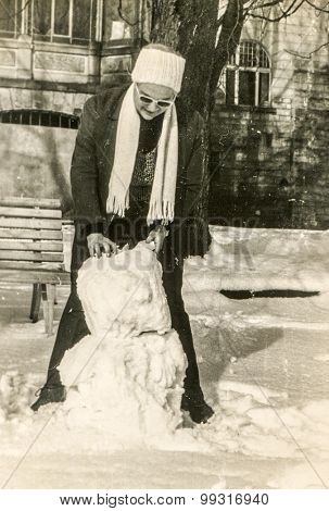 Vintage photo of woman making a snowman, 1950's
