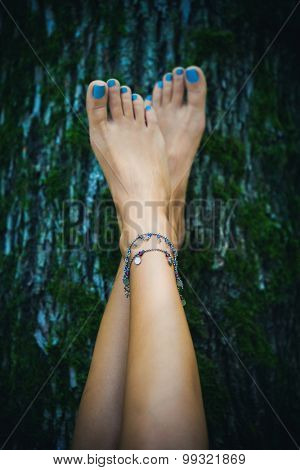 barefoot woman feet with ankle bracelets lean on tree with moss, natural light, selective focus poster