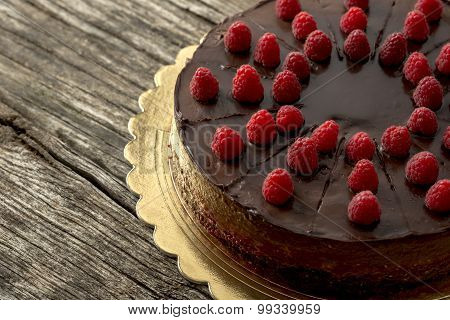 Overhead View Of Tasty Raw Chocolate Cake Decorated With Raspberries