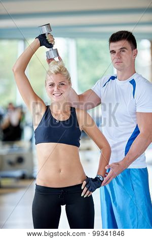 young sporty woman with trainer exercise weights lifting in fitness gym poster