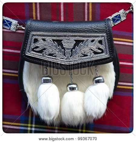 Traditional Scottish sporran with fur on a red tartan background.