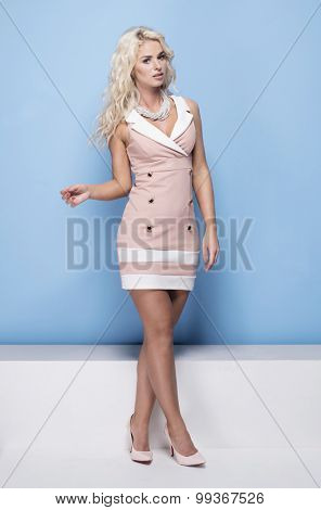 beauty, fashion and young woman in pink dress on blue background