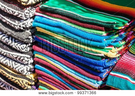 Colorful Mexican serapes hang in row.
